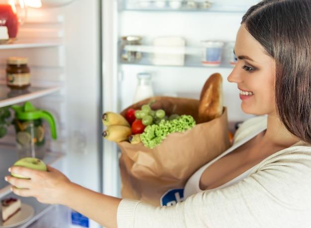 A mulher gravida está guardando um saco de papel com alimento.