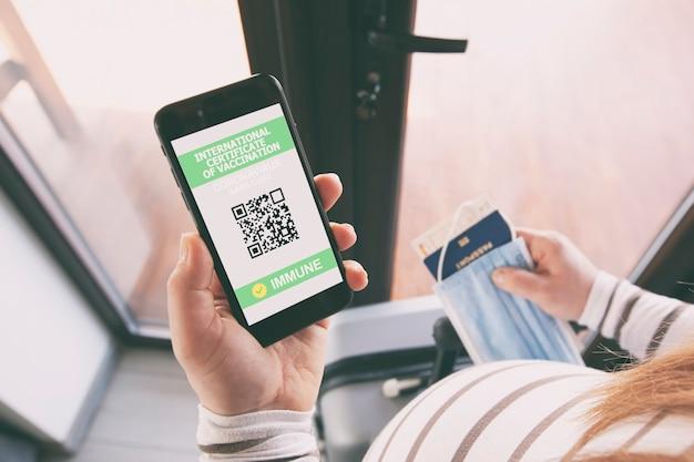 A mulher grávida mostrando o aplicativo passaporte digital de saúde no celular para viajar.