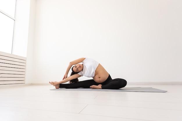 A mulher grávida se exercita propositalmente durante a aula de ioga e relaxa enquanto está sentada em uma esteira sobre o