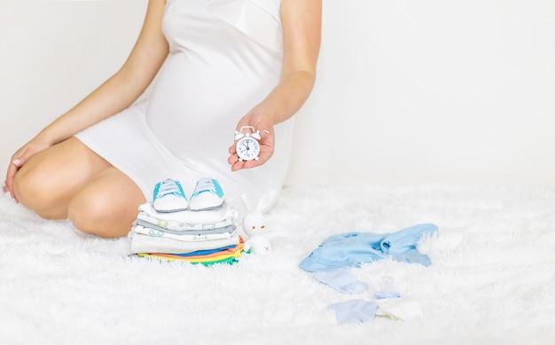 A mulher grávida tem um despertador nas mãos.