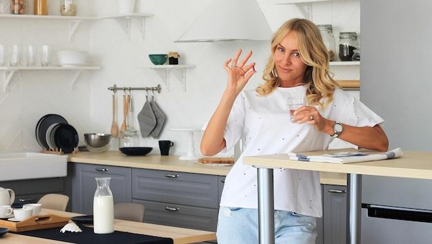 A mulher guarda o comprimido da vitamina e o vidro da água na cozinha da casa.