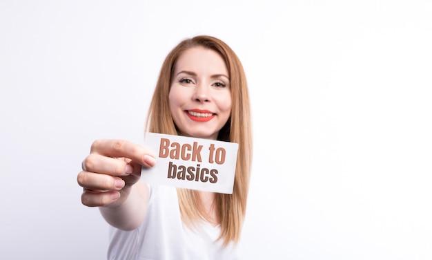 A mulher guarda um cartão com o texto voltar ao básico.