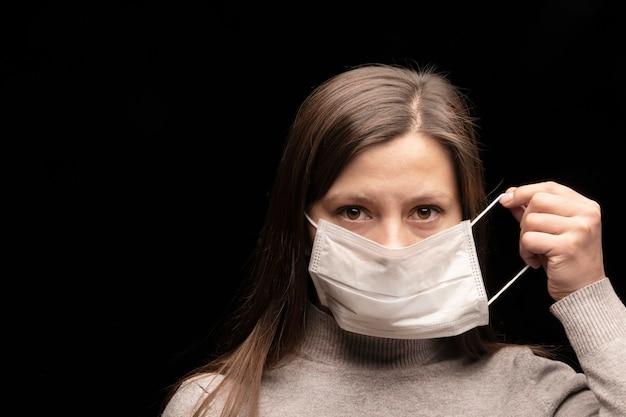 A mulher humana se veste e usa uma máscara protetora contra doenças infecciosas e como proteção contra a poluição ambiental e a gripe. propagação do coronavírus covid 2019.