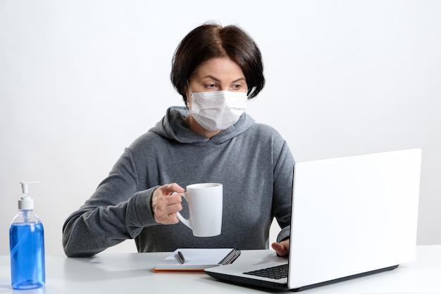 A mulher idosa em uma máscara protetora trabalha em um computador e bebe café