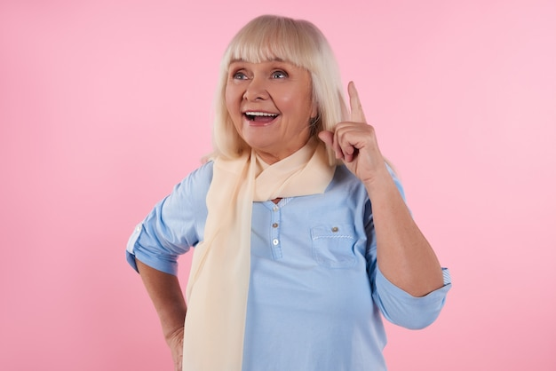 A mulher idosa está com o dedo indicador acima no fundo cor-de-rosa.