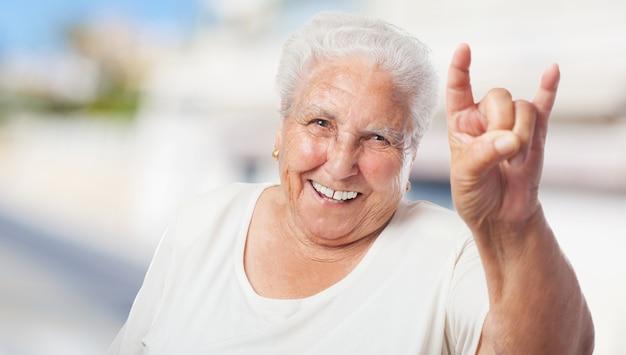 A mulher idosa que faz chifres com as mãos