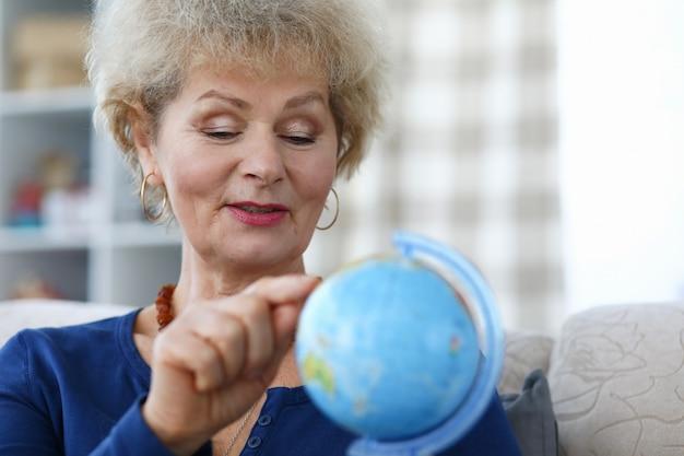 A mulher idosa segura o globo azul na mão e aponte para o continente com o dedo indicador.