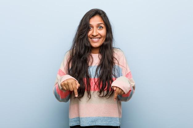 A mulher indiana da forma nova aponta para baixo com dedos, sentimento positivo.