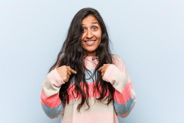 A mulher indiana da forma nova surpreendeu apontar-se, sorrindo amplamente.