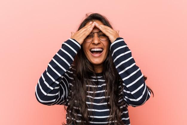 A mulher indiana intelectual nova cobre os olhos com as mãos, sorrisos amplamente à espera de uma surpresa.