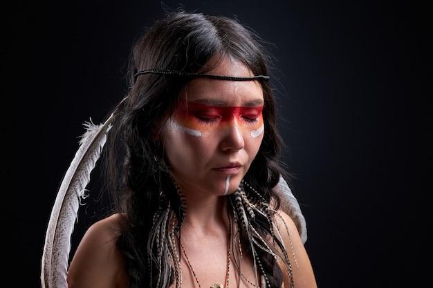 A mulher indiana mantém o equilíbrio mental, realiza rituais. jovem mulher com penas na cabeça e pinturas no rosto ficar com os olhos fechados, xamã. parede preta isolada