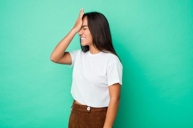 A mulher indiana nova da raça misturada isolou-se esquecendo algo, batendo na testa com palma e fechando os olhos.