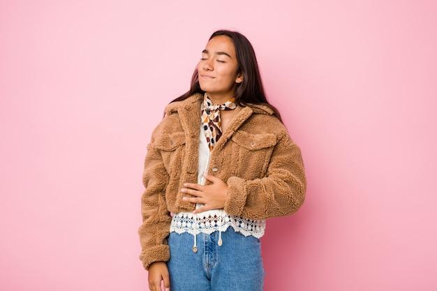 A mulher indiana nova da raça misturada que veste uma pele de carneiro curta acopla a barriga, sorri delicadamente, comendo e conceito da satisfação.