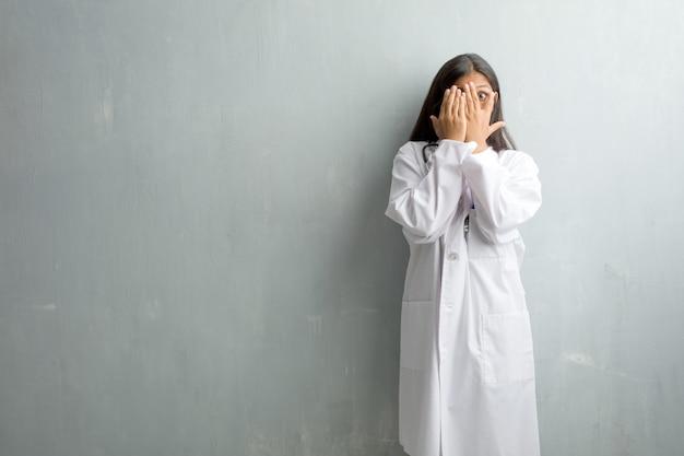 A mulher indiana nova do doutor de encontro a uma parede sente preocupada e scared, olhando e cobrindo um fa