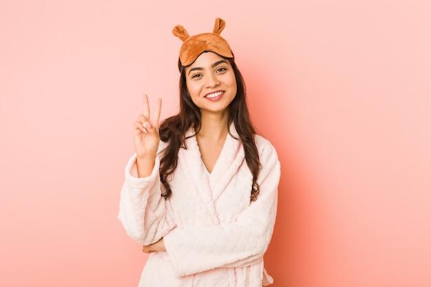 A mulher indiana nova que veste pijamas e máscara do sono isolou mostrar o número dois com dedos.