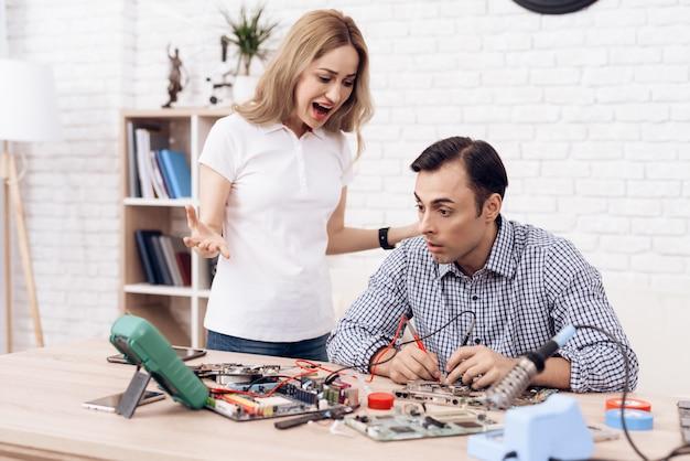A mulher irritada jura com mestre do marido em casa.