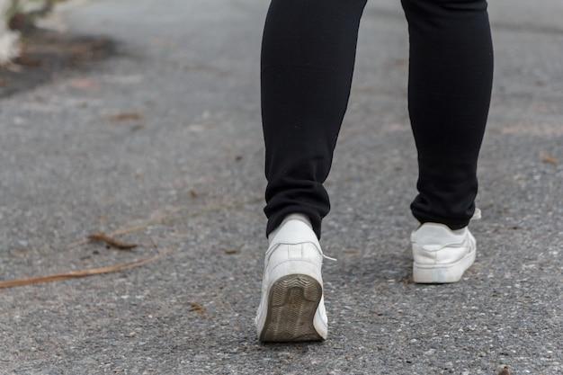 A mulher jeans e tênis andando na estrada.
