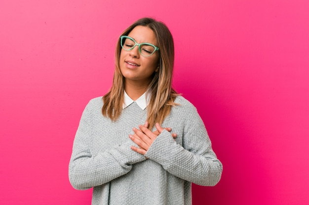 A mulher jovem, autêntica, carismática, real, contra uma parede tem uma expressão amigável, pressionando a palma da mão no peito. conceito de amor.