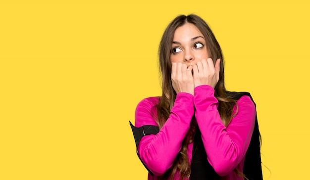 A mulher jovem do esporte está um pouco nervosa e assustada, colocando as mãos na boca sobre fundo amarelo isolado