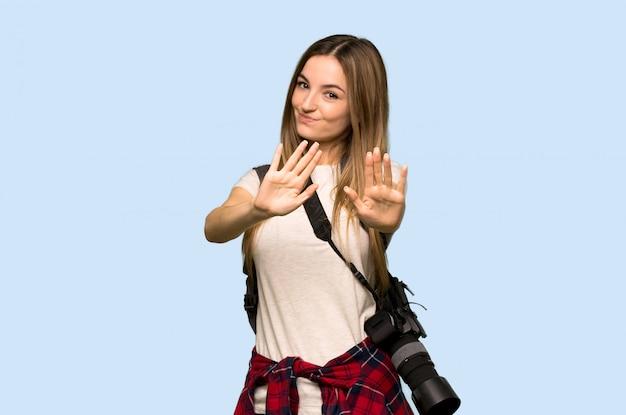 A mulher jovem fotógrafo está um pouco nervosa e assustada, esticando as mãos para a frente na parede azul