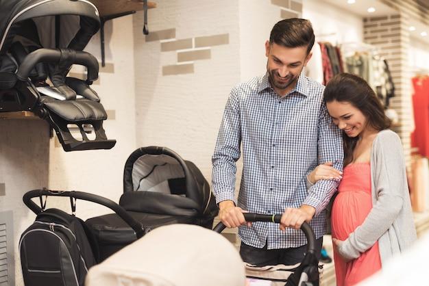 A mulher junto com um homem escolhe um carrinho de bebê.