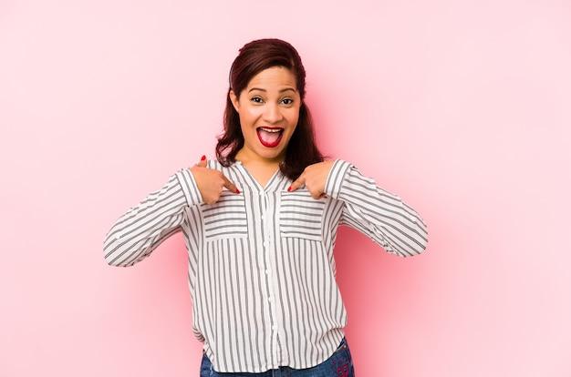 A mulher latin da idade média isolada em um fundo cor-de-rosa surpreendeu apontar com o dedo, sorrindo amplamente.