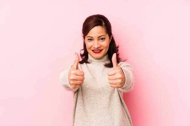 A mulher latin da idade média isolada em um fundo rosa com polegares levanta, felicidades sobre algo, apoia e respeita o conceito.