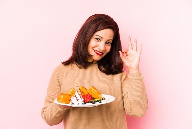 A mulher latin da idade média que guarda um waffle isolou alegre e confiável mostrando o gesto aprovado.