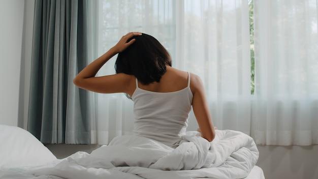 A mulher latino-americano adolescente acorda em casa. a menina asiática nova que estica após o sono acordado a noite toda que começa um dia novo com energia e vitalidade sentiu muito refrescada na cama perto da janela no quarto na manhã.