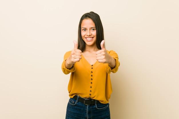 A mulher latino-americano nova contra uma parede bege com polegares levanta, elogios sobre algo, apoia e respeita o conceito.