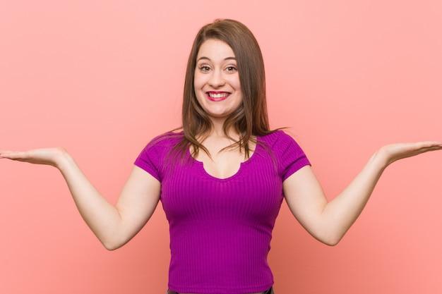 A mulher latino-americano nova contra uma parede cor-de-rosa faz a escala com braços, sente-se feliz e confiante.