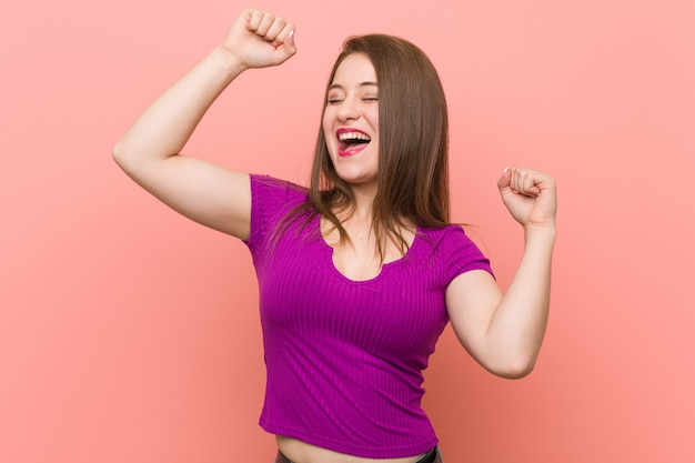 A mulher latino-americano nova contra uma parede cor-de-rosa que comemora um dia especial, salta e levanta os braços com energia.
