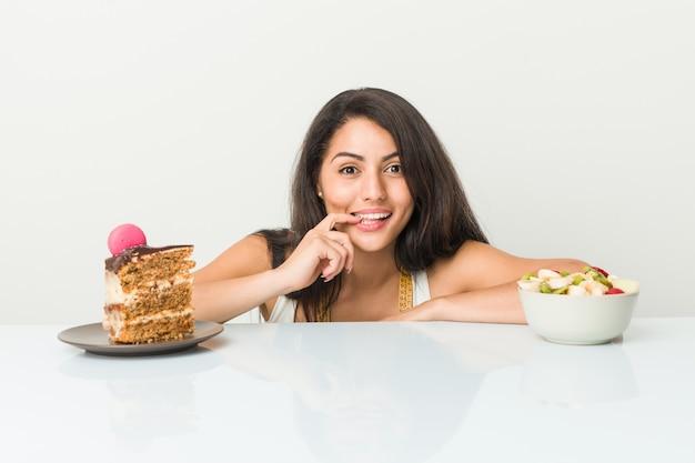 A mulher latino-americano nova que escolhe entre o bolo ou a fruta relaxou o pensamento sobre algo que olha uma cópia.