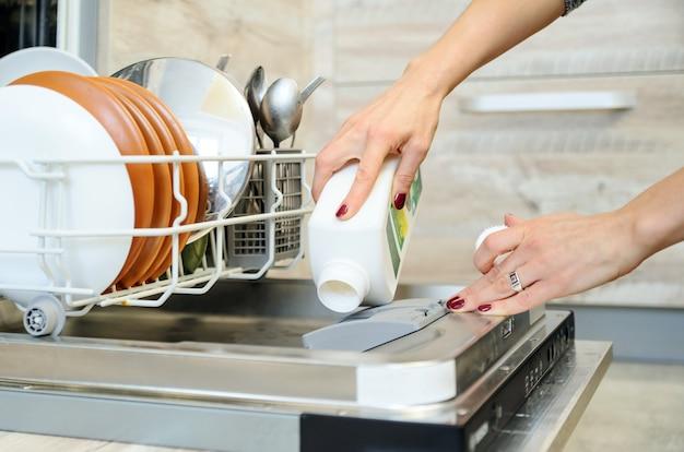 A mulher lava a louça na máquina de lavar louça.
