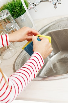 A mulher lava a xícara de chá
