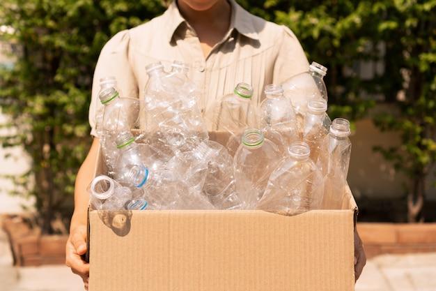 A mulher leva a caixa da garrafa plástica usada, reciclando o conceito plástico da utilização. problema ecológico, poluição ambiental. fechar-se