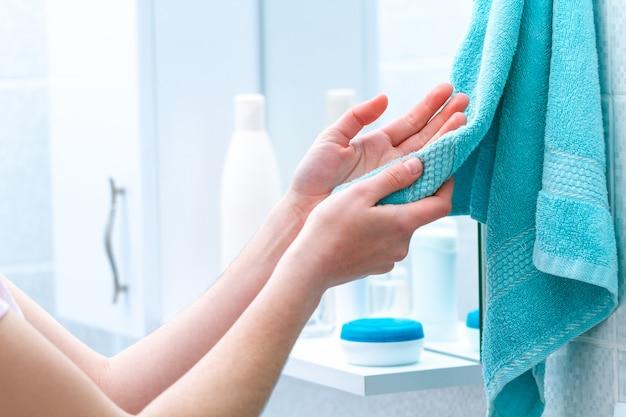 A mulher limpa as mãos secas com a toalha após a lavagem no banheiro em casa. higiene e cuidados com as mãos.