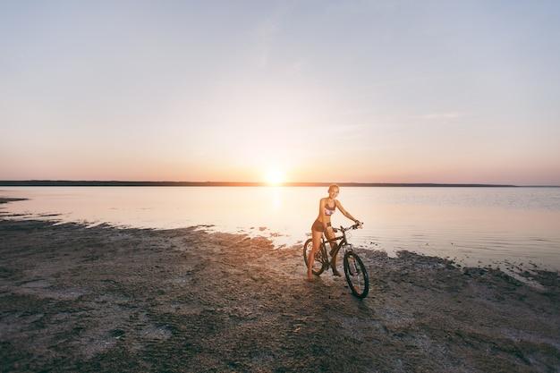 A mulher loira esportiva em um terno colorido anda de bicicleta em uma área deserta perto da água em um dia ensolarado de verão. conceito de aptidão.