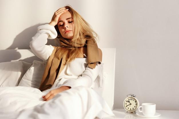 A mulher loira está deitada com um lenço na cama com dor de cabeça e febre