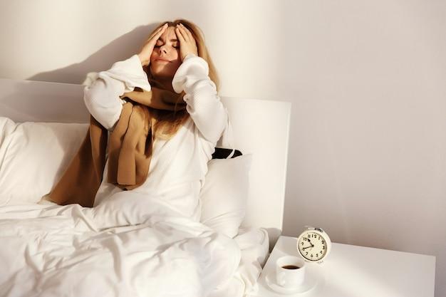 A mulher loira está deitada com um lenço na cama