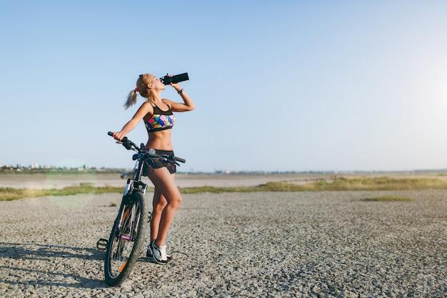 A mulher loira forte, de terno colorido e óculos escuros, fica perto de uma bicicleta, bebe água de uma garrafa preta em uma área deserta. conceito de aptidão.