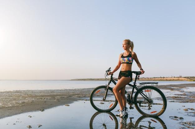 A mulher loira forte em um terno colorido está perto de uma bicicleta em uma área deserta perto da água. conceito de aptidão.