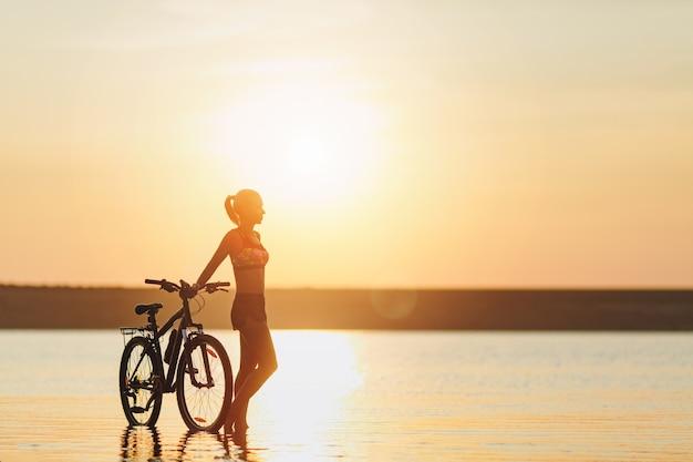 A mulher loira forte em um terno colorido fica perto da bicicleta na água ao pôr do sol em um dia quente de verão. conceito de aptidão.