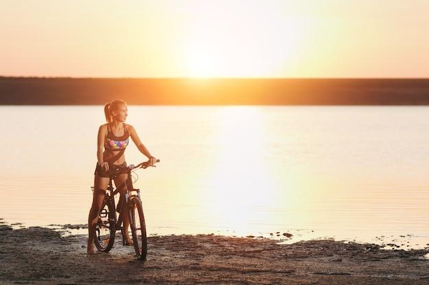 A mulher loira forte em um terno colorido senta-se na bicicleta perto da água ao pôr do sol em um dia quente de verão. conceito de aptidão.