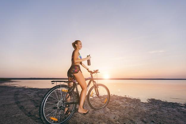 A mulher loira forte em um terno colorido senta-se na bicicleta, segura uma garrafa preta com água em uma área deserta perto da água. conceito de aptidão.