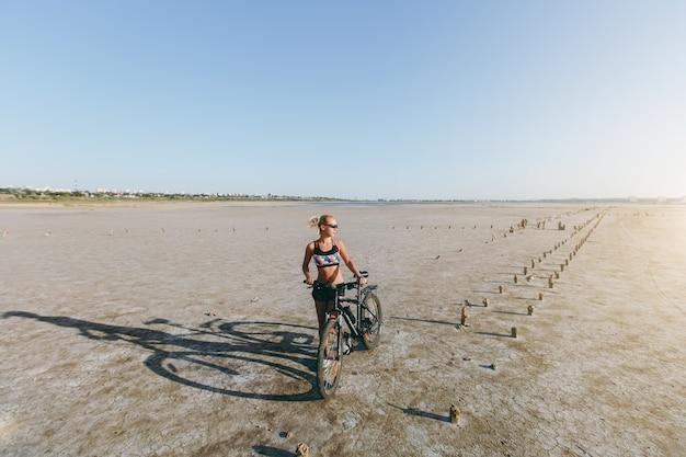 A mulher loira forte em um terno multicolorido e óculos escuros está perto de uma bicicleta em uma área deserta e olha para o sol. conceito de aptidão.