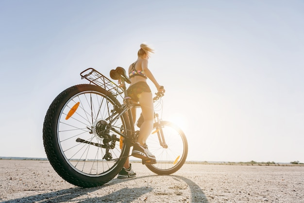 A mulher loira forte em um terno multicolorido senta-se em uma bicicleta em uma área deserta e olha para o sol. conceito de aptidão. vista traseira. fechar-se