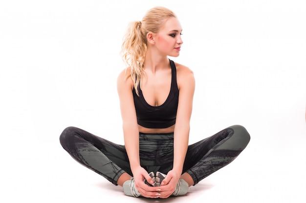 A mulher loura bonita na parte superior preta faz exercícios isolados no branco