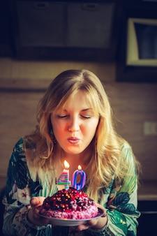 A mulher loura caucasiano feliz bonita comemora 40 aniversários.