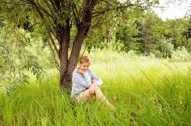 A mulher loura caucasiano senta-se na grama em um prado ao lado de uma árvore.